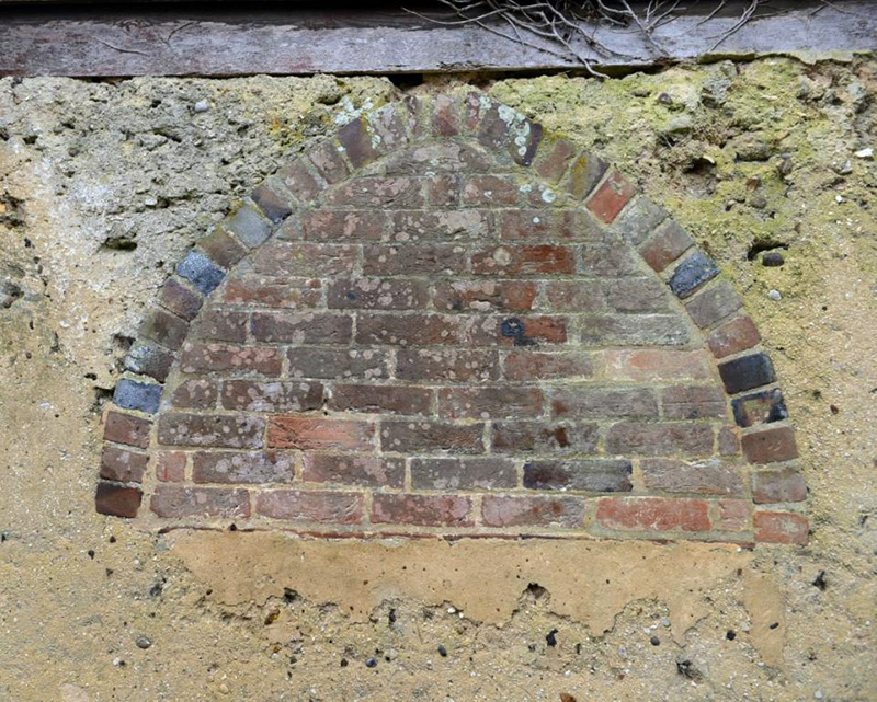 The bricked-up arched window in north elevation